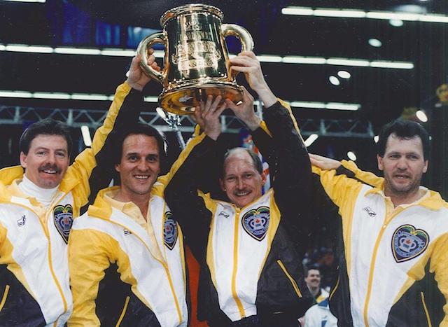Les champions du Brier 1992 soulèvent le trophée. De gauche à droite : Vic Peters, Dan Carey, Chris Neufeld et Don Rudd (photo de l'ACC)