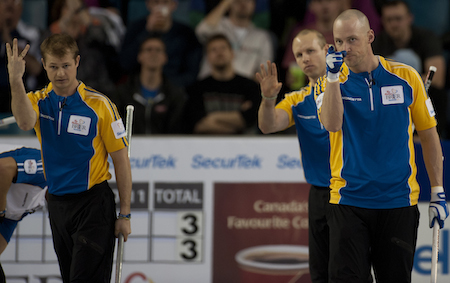 Carter Rycroft, Pat Simmons and Nolan Thiessen congratulate Kevin Koe on his shot for three in the fifth end. (Photo, CCA/Michael Burns)