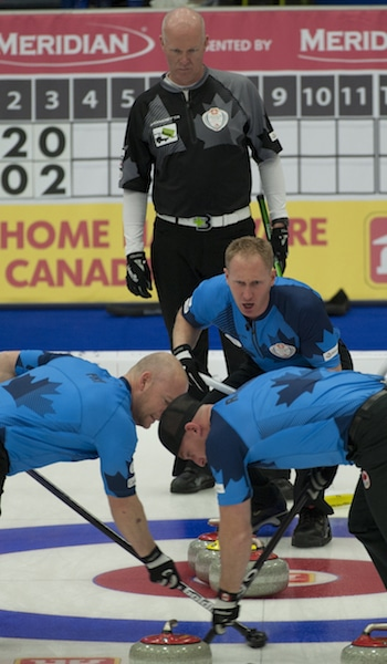 Brad Jacobs guides sweepers Ryan Fry, left, and Ryan Harnden with Glenn Howard looking on. (Photo, CCA/Michael Burns)