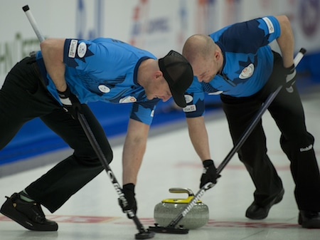 Ryan Harnden, left, and Ryan Fry scrub a rock during their team's win over Mike McEwen on Friday. (Photo, CCA/Michael Burns)
