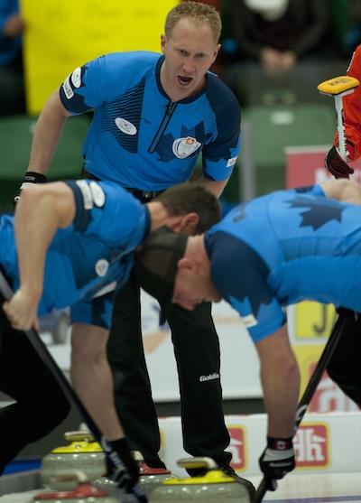 Brad Jacobs encourages sweepers E.J. Harnden, left, and Ryan Harnden. (Photo, CCA/Michael Burns)