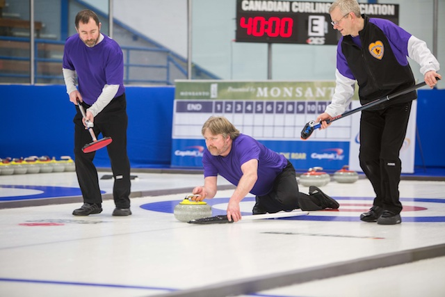 Yukon's Doug Hamilton delivers his rock with sweepers Dale Enzenauer and Doug Gee in Draw 3 action at the 2014 Canadian Senior Curling Championships in Yellowknife (Photo James MacKenzie)