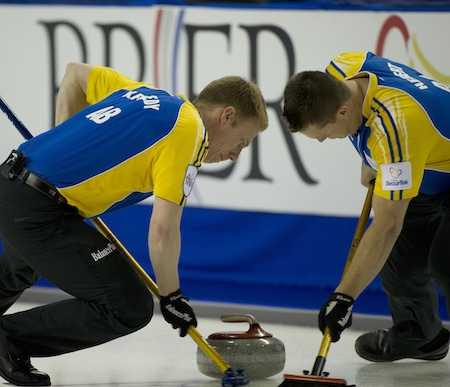Alberta's Marc Kennedy, left, and Ben Hebert sweep during their win over New Brunswick on Friday. (Photo, Curling Canada/Michael Burns)