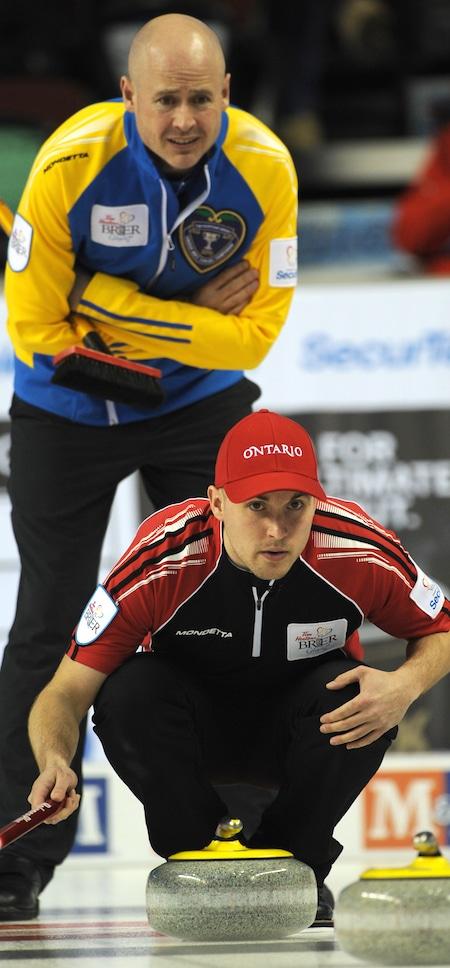 Alberta skip Kevin Koe, top, peers over the shoulder of Ontario skip Mark Kean during their game on Sunday night. (Photo, Canadian Curling/Michael Burns)