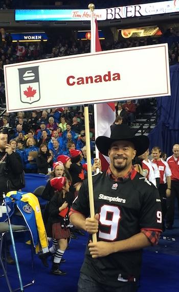 Calgary Stampeders running back Jon Cornish leads Team Canada onto the ice on Tuesday night. (Photo, Curling Canada/Michael Burns).