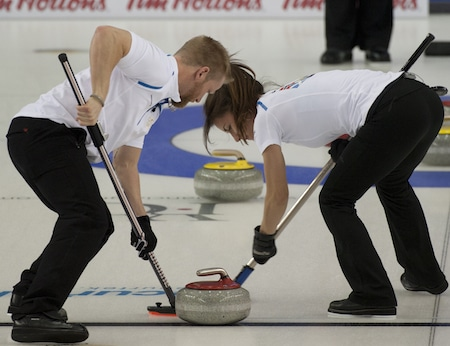Niklas Edin, left, and Anna Sidorova sweep a rock in mixed doubles play on Thursday. (Photo, CCA/Michael Burns)