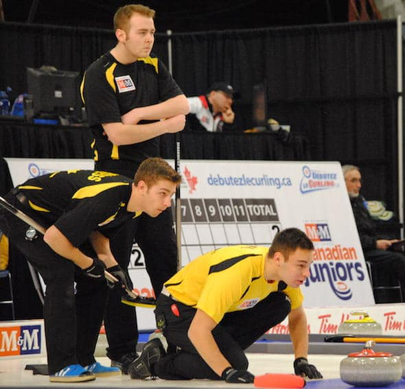 Manitoba third Kyle Kurz, right, calls sweeping instructions to his teammates as New Brunswick skip Rene Comeau, top, and third Andrew Burgess look on. (Photo, Amanda Rumboldt)