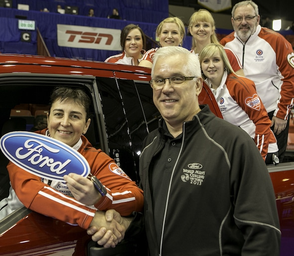 Heather Strong, left, with her Newfoundland/Labrador teammates behind her, is congratulated on winning the lease on a 2015 Ford F-150 XLT by Gerald Wood, General Manager, Western Region for Ford of Canada. (Photo, CCA/Andrew Klaver)
