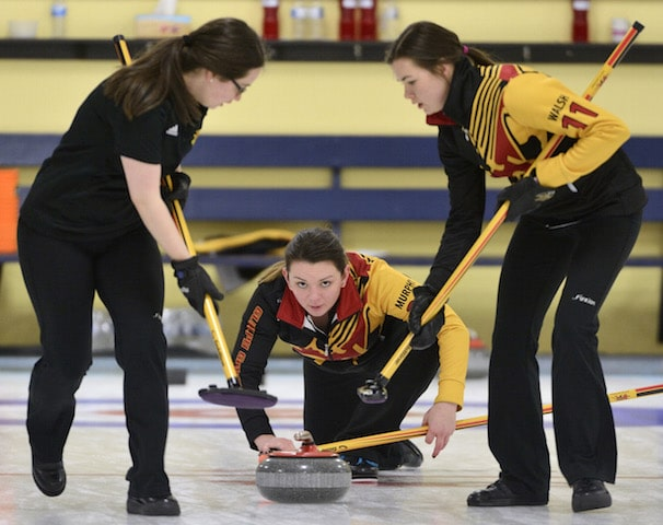 University of Guelph 's Jestyn Murphy watches her rock as sweepers Heather Cridland and Emily Walsh watch during opening day action at the CIS/CCA Curling Championships in Waterloo, Ont. (Photo Adam Gagnon)