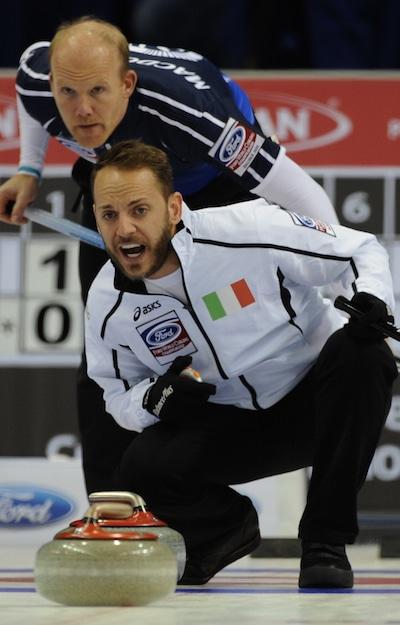 Italian skip Joel Retornaz, bottom, calls instructions to sweepers as Scottish skip Ewan MacDonald looks on. (Photo, Curling Canada/Michael Burns)