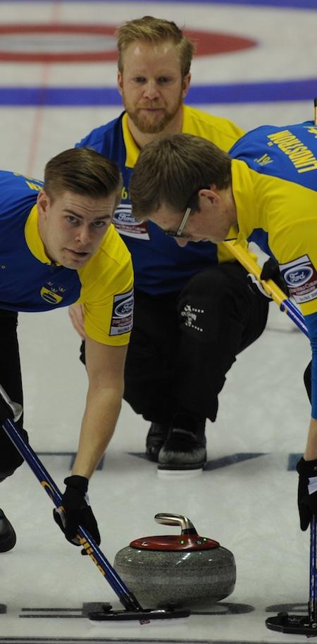 Swedish skip Niklas Edin looks on as teammates Christoffer Sundgren, left, and Kristian Lindström sweep his rock. (Photo, Curling Canada/Michael Burns)