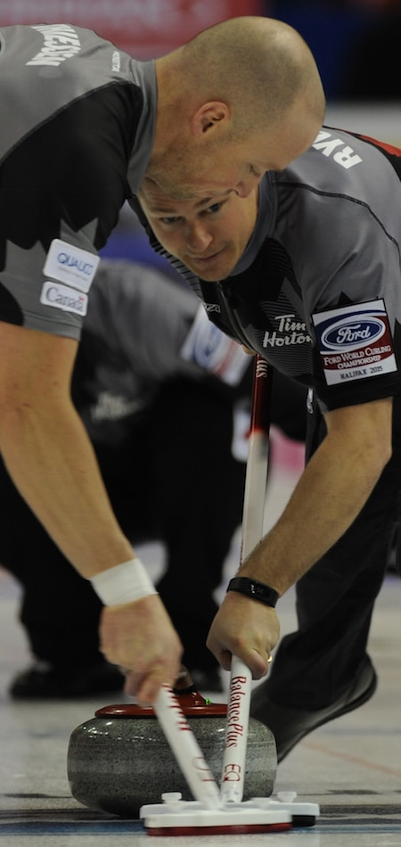 Team Canada's Nolan Thiessen, left, and Carter Rycroft go to work during Sunday's win over China. (Photo, Curling Canada/Michael Burns)
