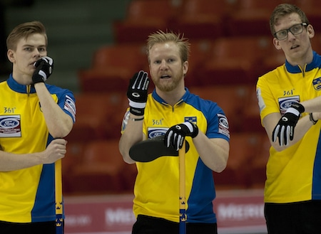 Sweden skip Niklas Edin, middle, discusses strategy with teammates Christoffer Sundgren, left, and Kristian Lindström. (Photo, Curling Canada/Michael Burns)