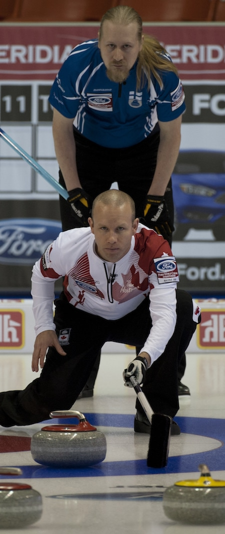 Canada's Pat Simmons checks out a shot with Finland's Aku Kauste looking over his shoulder. (Photo, Curling Canada/Michael Burns)
