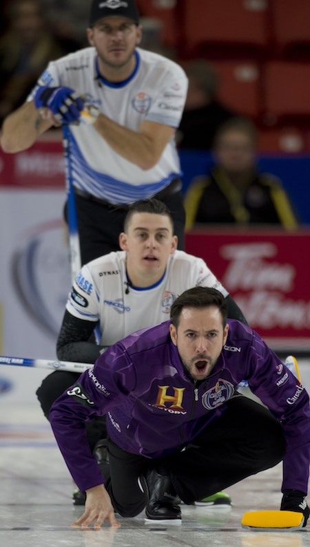 John Epping watches his shot as Team Carruthers' Derek Samagalski, top, and Colin Hodgson look on.