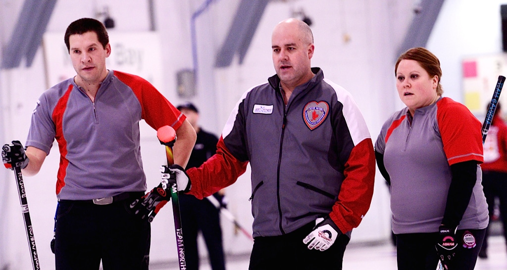 Robert Borden, Jamie Koe et Kerry Galusha des Territoires du Nord-Ouest parlent stratégie durant leur match de 11e ronde contre l'Ontario au Championnat canadien 2015 de curling mixte à North Bay, Ont. (Brian Doherty Photography)
