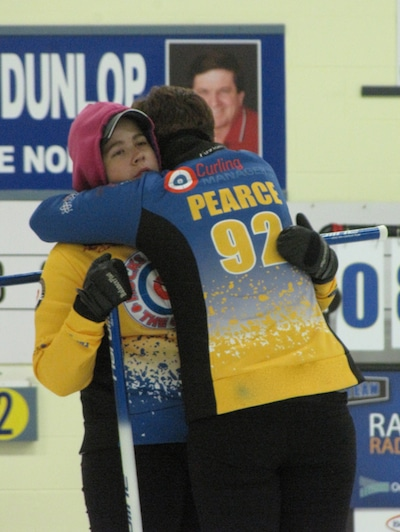 After 40 hours of continuous curling Amanda Pearce (facing camera) gets an encouraging hug from her twin sister Brittany. The 22-year-olds are the only women in Canada to have beaten two world records for the longest curling game (Photo Clarissa Yahn)