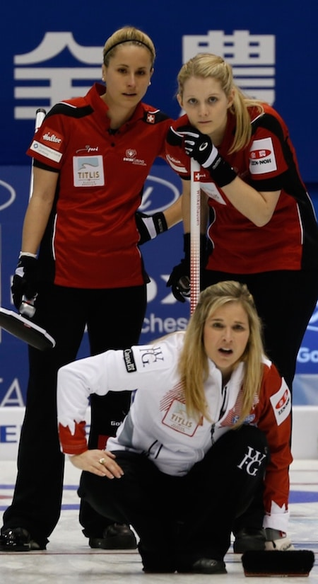 Jennifer Jones du Canada regarde son tir que Nicole Schwägli de la Suisse, à gauche, et Marisa Winkelhausen regardent. (Photographie, WCF / Richard Gray)