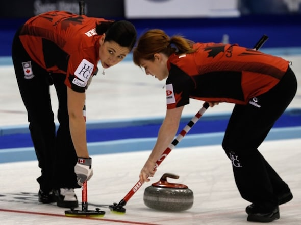 Jill Officer d'Équipe Canada, à gauche, et Dawn McEwen balaient un rocher lors de la victoire de lundi sur la Chine. (Photo, WCF / Richard Gray)
