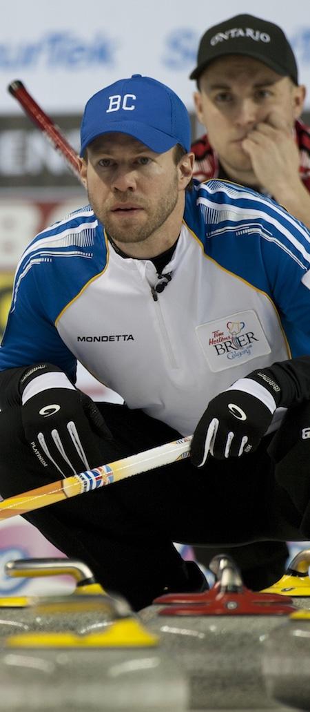 Colombie-Britannique capitaine Jim Cotter sauter, à gauche, un coup montres que l'Ontario capitaine Mark Kean regarde. (Photo, Curling Canada / Michael Burns)