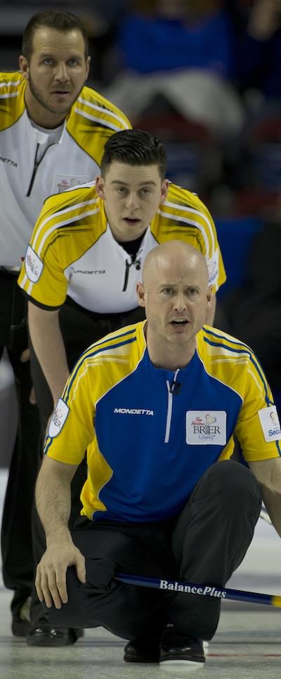 Alberta sauter Kevin Koe appelle les instructions que Derek Samagalski du Manitoba, en haut, et Colin Hodgson regardent. (Photo, Curling Canada / Michael Burns)