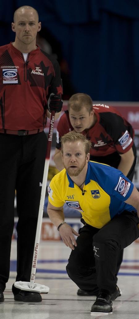 Suède capitaine Niklas Edin montres son tir que Nolan Thiessen d'Équipe Canada, à gauche, et Carter Rycroft regardent. (Photo, Curling Canada / Michael Burns)