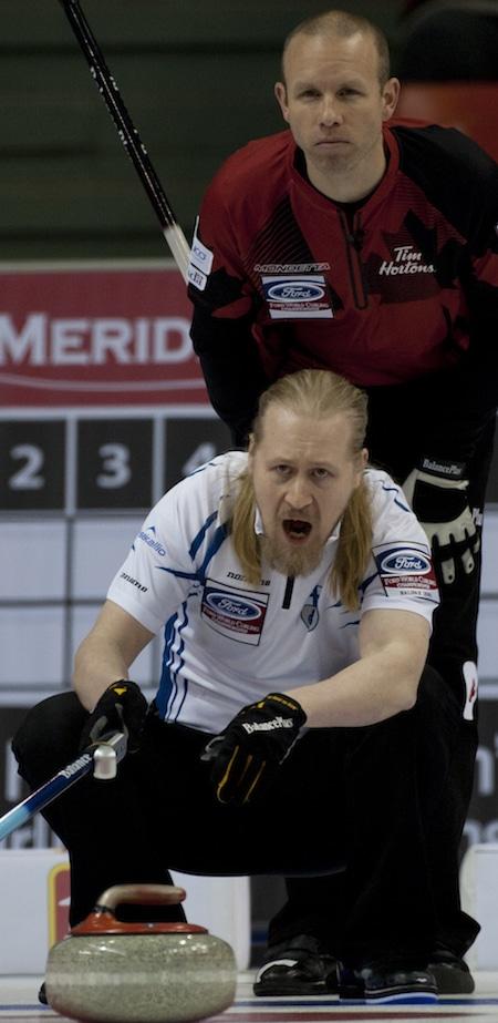Aku Kauste de la Finlande appelle à ses balayeuses, comme Pat Simmons du Canada regarde par dessus son épaule. (Photo, Curling Canada / Michael Burns)