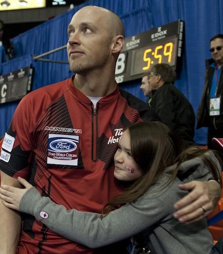 Nolan Thiessen du Canada reçoit l'accolade après-match de la fille Tyra après avoir remporté la médaille de bronze, dimanche. (Photo, Curling Canada / Michael Burns)
