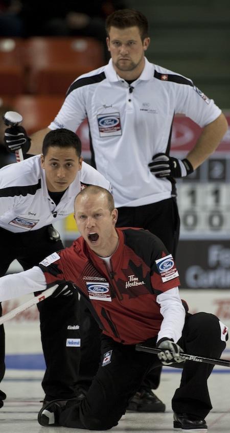 Équipe Canada capitaine Pat Simmons appelle des instructions pour que les balayeuses Enrico Pfister de la Suisse, à gauche, et Reto Keller regardent. (Photo, Curling Canada / Michael Burns)