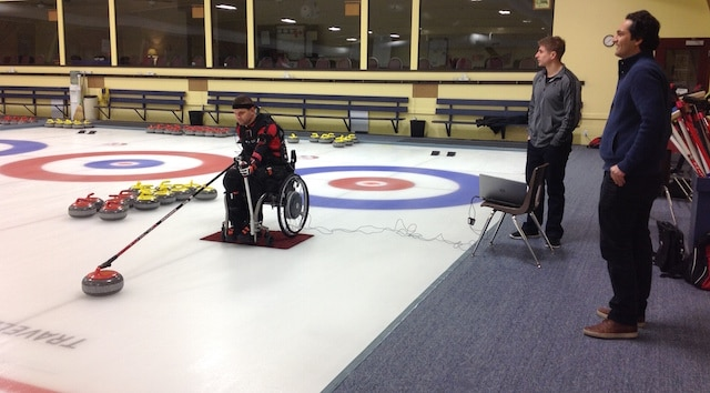 """Paralympian Mark Ideson delivers a stone using a """"suit"""" of sensors, as University of Waterloo Master's Engineering student Brock Laschowski and Dr. Naser Mehrabi observe (Photo courtesy of Dr. John McPhee)"""