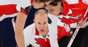 Team Canada's Chris Haichert watches his rock as sweepers Jolene Campbell and Teejay Haichert get to work (Photo WCF/ Céline Stucki)