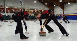 Marie Christianson et Lauren Wasylkiw (Terre-Neuve) se mettent au travail avec les brosses durant le Championnat canadien 2016 de curling mixte à Toronto (Photo de Curling Canada/Sonja DiMarco)