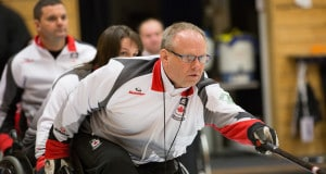 Team Canada second Dennis Thiessen delivers his rock assisted by third Ina Forrest and lead Mark Ideson at the World Wheelchair Curling Championships, Lucerne, Switzerland (WCF/Céline Stucki photo)