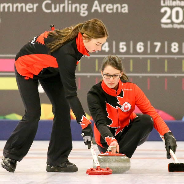 Canadian skip Mary Fay delivers her rock while second Karlee Burgess prepares to sweep at the 2016 Youth Olympic Games in Lillehammer, Norway (WCF/Richard Gray photo)