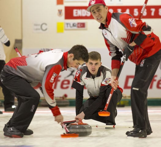 Team Canada alternate Wade Ford throws his rock to sweepers Colton Lott and Kyle Doering at the 2016 World Junior Curling Championship (WCF/Marissa Tiel photo)