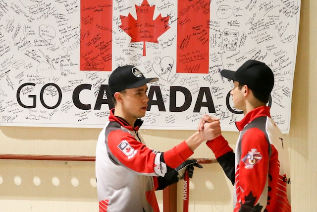Team Canada's Kyle Doering and Colton Lott celebrate in front of the Canadian flag at the Taarnby Curling Club during the 2016 World Junior Curling Championships (WCF/Richard Gray)