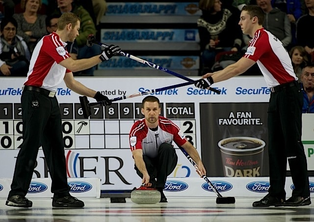 Team Gushue front end Geoff Walker (left) and Brett Gallant (right) swap brooms during action at the 2016 Tim Hortons Brier in Ottawa (Curling Canada/Michael Burns photo)