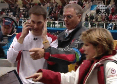 """""""Mom, pick up the phone…"""" Moments after winning the gold medal at the Winter Olympics in Torino, Italy, skip Brad Gushue tries to connect with his mom back home in Newfoundland. (Screenshot from CBC.ca)"""