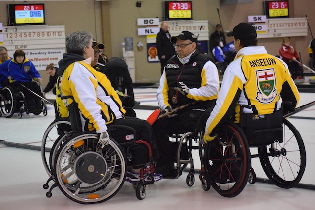 Team Manitoba listens to skip Mark Thiessen during a huddle on the ice at the 2016 Canadian Wheelchair Championship in Regina (Curling Canada/Morgan Daw photo)
