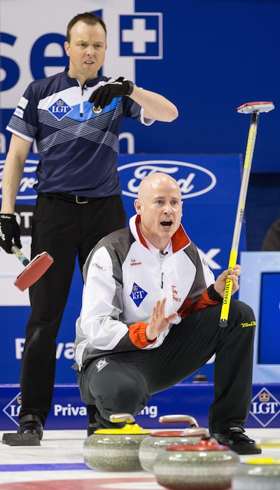 Canada's Kevin Koe, below, calls instructions to sweepers as Scotland's Tom Brewster looks on. (Photo, World Curling Federation/Céline Stuckli)