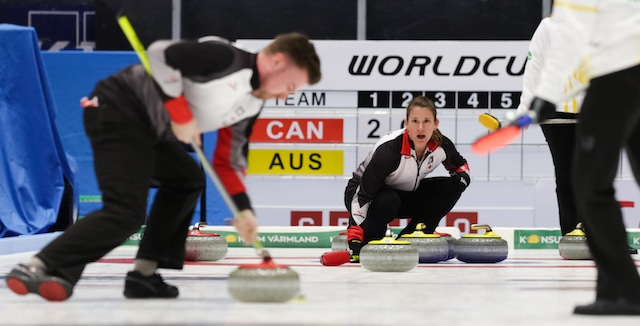 Marliese Kasner calls the line as teammate Dustin Kalthoff sweeps during action at the 2016 World Mixed Doubles Curling Championship in Karlstad, Sweden (WCF/Hamish Irvine photo)