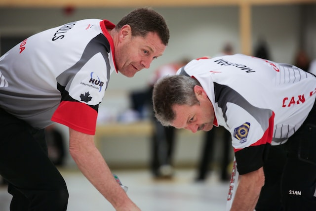 Peter Nicholls and Dean Moxham sweep hard to get a rock into the rings at the 2016 World Seniors Curling Championships in Karlstad, Sweden (WCF/Céline Stucki photo)