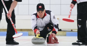 Canadian skip Randy Neufeld delivers his rock while sweepers Dean Moxham and Dale Michie prepare to sweep at the 2016 World Senior Curling Championships in Karlstad, Sweden (WCF/Céline Stucki photo)