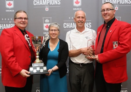 Nova Scotia won the Governors' Cup. Governors Hugh Avery, left, and Scott Comfort, right, present the Governors' Cup to Cathy Dalziel and Harry Daemen of the Nova Scotia Curling Association. (Photo, Curling Canada/Neil Valois)