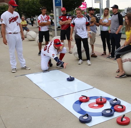 Winnipeg Goldeyes pitcher Duke Von Schamann attempts an in-turn takeout in his introduction to curling, encouraged by teammate Jacob Rogers and several of Manitoba's elite young curlers. (Photo, courtesy Winnipeg Goldeyes).