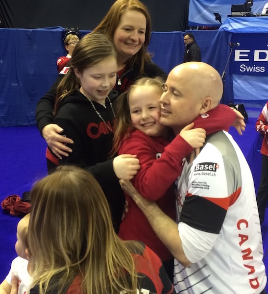 Kevin Koe shares a moment of celebration with wife, Carla, and their two daughters after winning the gold medal at the 2016 World Men's Curling Championship in Basel, Switzerland (Curling Canada photo)