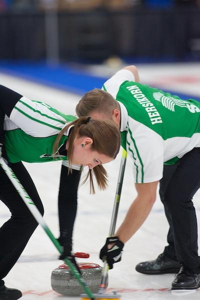 Les brosseurs de la Saskatchewan Jacob Hersikorn et Krista Fesser travaillent fort. (Curling Canada/Robert Wilson photo)
