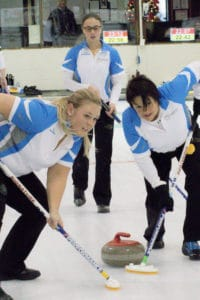 Team Quebec second Laurie Verreault and lead Sylvie Cote sweep skip Nathalie Gagnon's rock during action at the 2016 Travelers Curling Club Championship in Kelowna, B.C. (Curling Canada/Jessica Krebs photo)