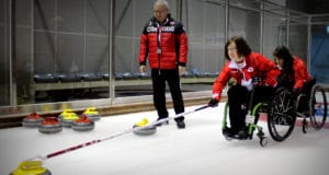 Marie Wright pracitces in Korea while coach Wayne Kiel looks on. Photo by Brian Chick (Curling Canada)