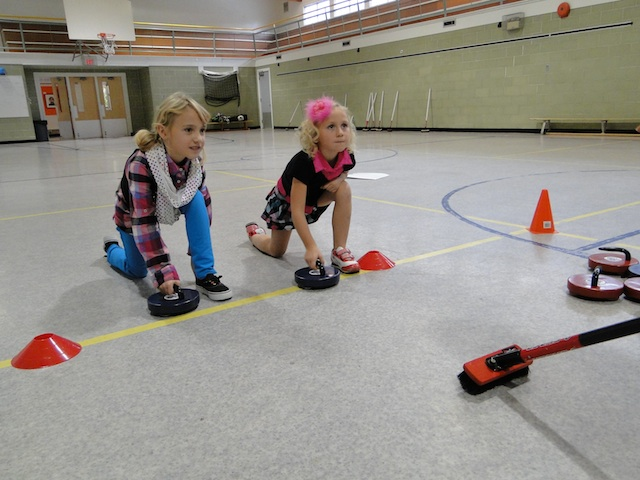 Two new curlers practice hitting the broom (Photo courtesy Rocks & Rings)